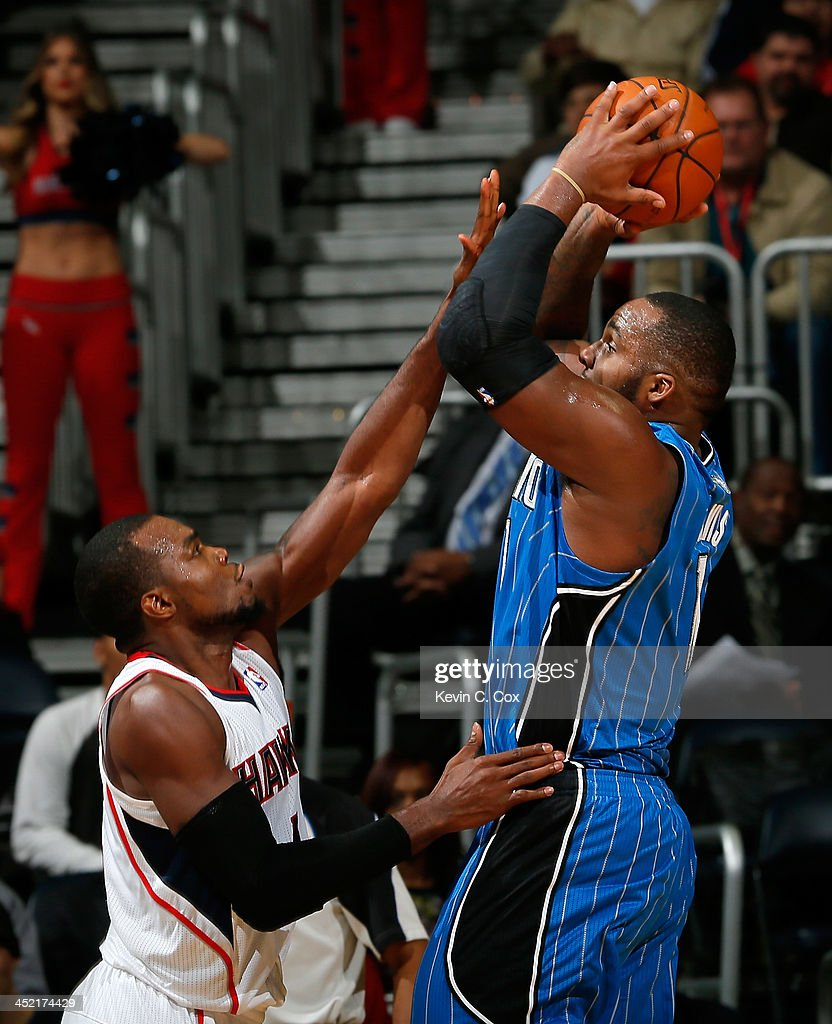 Glen Davis #11 of the Orlando Magic shoots over Paul Millsap #4 of the Atlanta Hawks at Philips Arena on November 26, 2013 in Atlanta, Georgia.