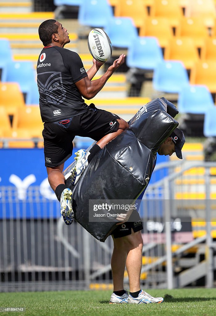 Glen Fisiiahi of the Warriors takes a high ball with Warriors assistant coach Andrew McFadden holdin the pads during a New Zealand Warriors NRL training session at Mt Smart Stadium on April 2, 2014 in Auckland, New Zealand.