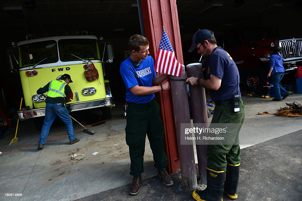 Glen Haven firefighters Michael Ryan, in blue and TJ Doherty, put up a small American Flag at their station in Glen Haven, CO, on September 17, 2013. The small mountain town of Glen Haven north east of Estes Park has been wiped out by the recent and massive flooding.