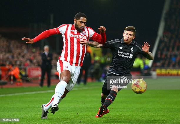 Glen Johnson of Stoke City and Alberto Moreno of Liverpool battle for the ball during the Capital One Cup semi final first leg match between Stoke...