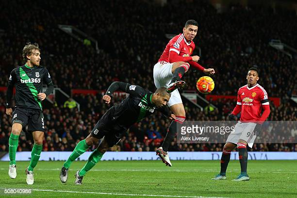 Glen Johnson of Stoke City and Chris Smalling of Manchester United compete for the ball during the Barclays Premier League match between Manchester...