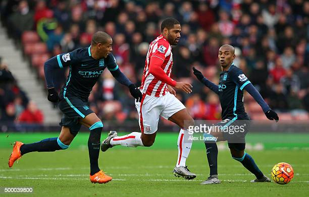 Glen Johnson of Stoke City competes for the ball against Fernando and Fernandinho of Manchester City during the Barclays Premier League match between...