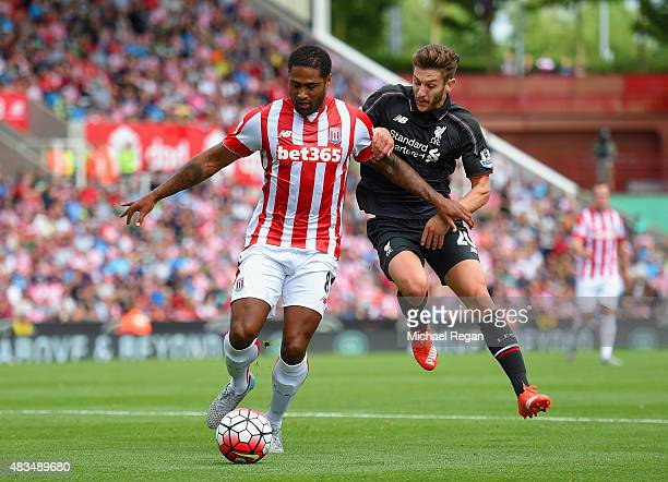 Glen Johnson of Stoke City holds off Adam Lallana of Liverpool during the Barclays Premier League match between Stoke City and Liverpool at Brittania...