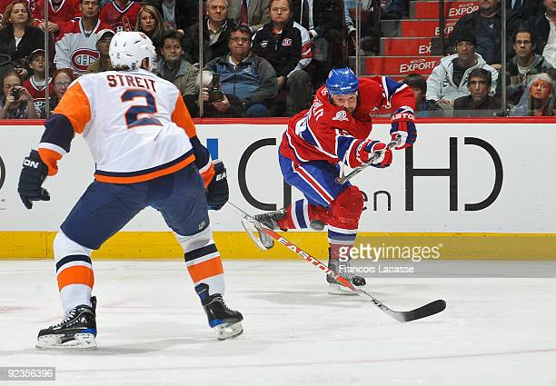 Glen Metropolit of the Montreal Canadiens takes a shot in front of Mark Streit of the New York Islanders during the NHL game on October 26 2009 at...