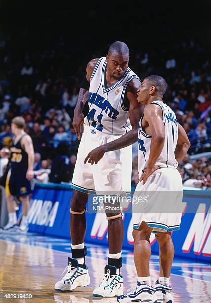 Glen Rice of the Charlotte Hornets talks to Muggsy Bogues during a game against the Indiana Pacers circa 1997 at the Charlotte Coliseum in Charlotte...
