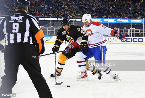 Glen Wesley of the Boston Bruins Alumni Team and Alexei Kovalev of the Montreal Canadiens Alumni Team vie for the puck during the Alumni Game as part...