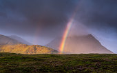 I shot this during a down pour of rain one misty morning while travelling through Glencoe, Scotland. The sun burst through the cloud to create the rainbow in front of the Munro Creise.