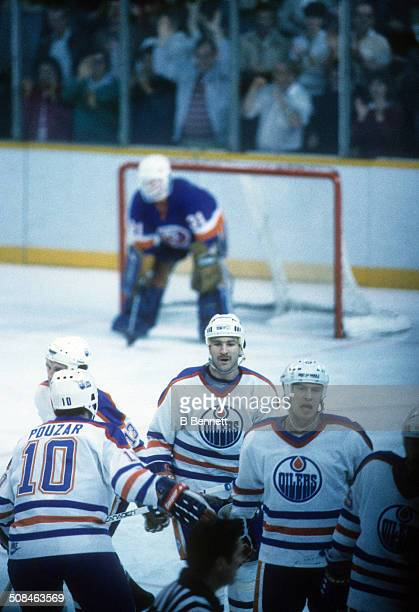 Glenn Anderson and Mark Messier of the Edmonton Oilers celebrate with teammates after scoring a goal as goalie Billy Smith of the New York Islanders...