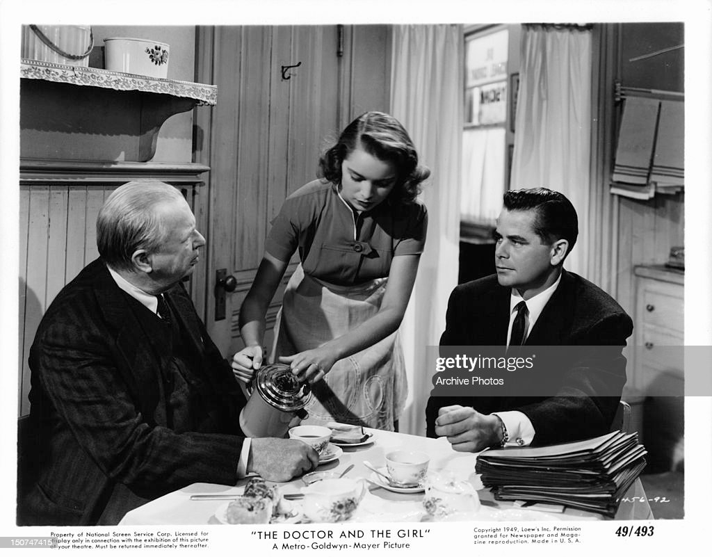 Glenn Ford and unknown actor sit at a kitchen table as Nancy Davis pours coffee in a scene from the film 'The Doctor And The Girl' 1949