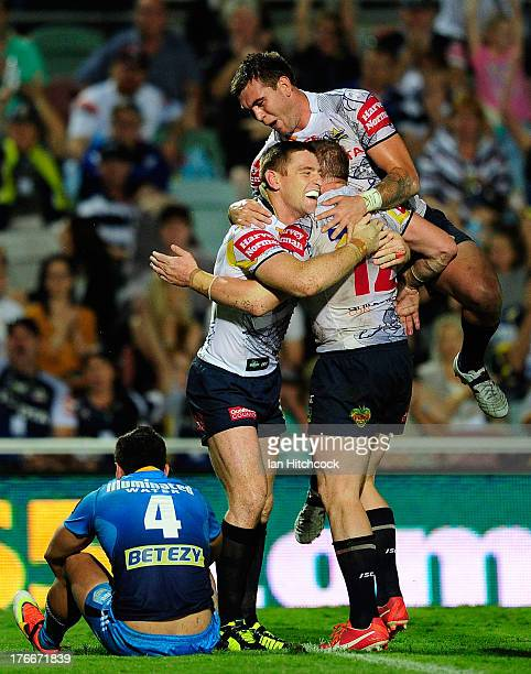 Glenn Hall of the Cowboys celebrates with Brent Tate and Kyle Feldt after scoring a try during the round 23 NRL match between the North Queensland...