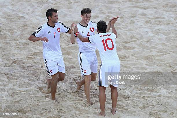 Glenn Hodel of Switzerland celebrates with teammates Philipp Borer and Sandro Spaccarotella after scoring during the beach soccer first round Group A...