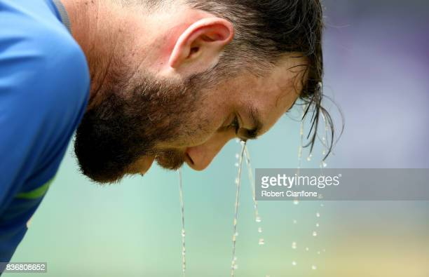 Glenn Maxwell of Australia pours water over his head during an Australian Test team nets session at SherE Bangla National Cricket Stadium on August...