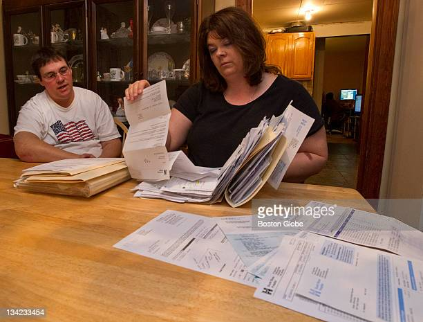 Glenn McCarthy and his wife Tracy McCarthy in their home with a pile of medical bills that they are unable to pay since their health insurance...