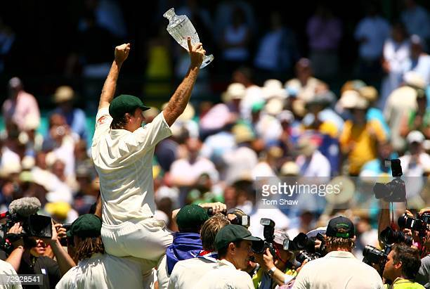 Glenn McGrath of Australia celebrates on the shoulder of Stuart Clark and Andrew Symonds with the Ashes trophy after winning the final test and...