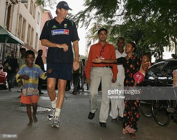 Glenn McGrath of Australia meets local residents on the streets of Mumbai on October 13 in Mumbai India
