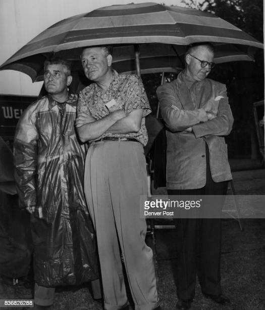 Glenn Miller Story Three members of a movie company shooting scenes for 'The Glenn Miller Story' stare glumly at rain which washed out Thursday...