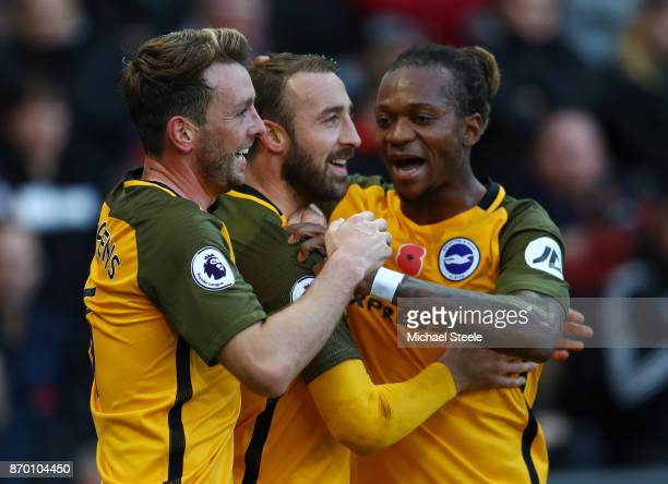 Glenn Murray celebrates scoring his side's first goal with Dale Stephens and Gaetan Bong of Brighton and Hove Albion during the Premier League match...