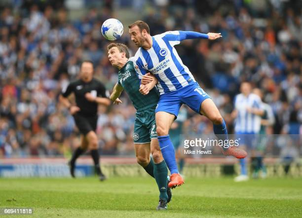Glenn Murray of Brighton and Hove Albion challenges for the ball with Stephen Warnock of Wigan during the Sky Bet Championship match between Brighton...