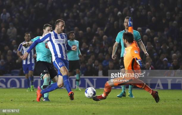 Glenn Murray of Brighton and Hove Albion shoots past goalkeeper Scott Carson of Derby County to score their third goal during the Sky Bet...