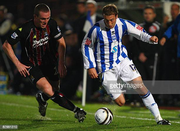 Glenn Murray of Brighton and Hove Albion takes on Richard Dunne of Manchester City during the Carling Cup Second Round match between Brighton and...