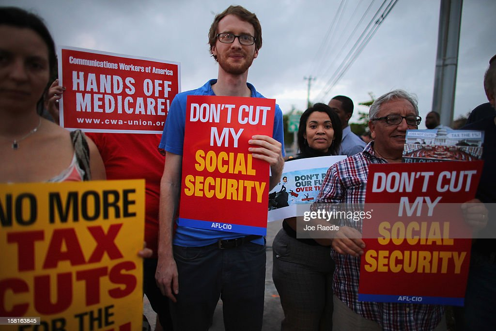 Glenn Rehn (C) and other protesters rally together outside the office of U.S. Sen. Marco Rubio (R-FL) on December 10, 2012 in Doral, Florida. The protesters are hoping that Senators like Rubio will not cut medicare/social security benefits and will agree to raise taxes on the top 2% of earners in the country.