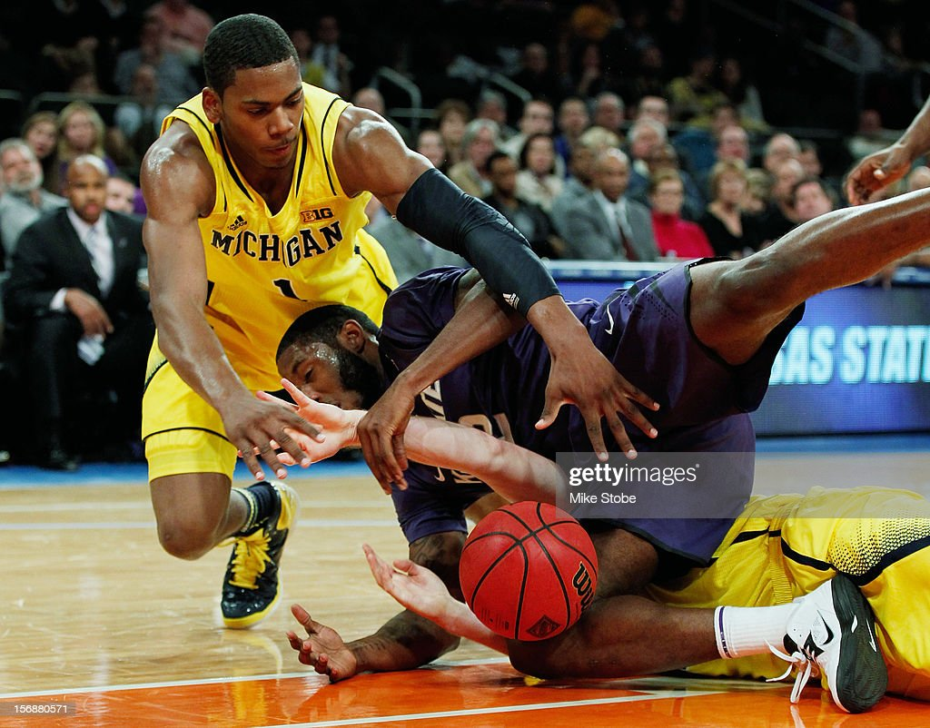 Glenn Robinson III #1 of the Michigan Wolverines battles for the loose ball with Thomas Gipson #42 of the Kansas State Wildcats at Madison Square Garden on November 23, 2012 in New York City. Michigan Wolverines defeated Kansas State Wildcats 71-57.
