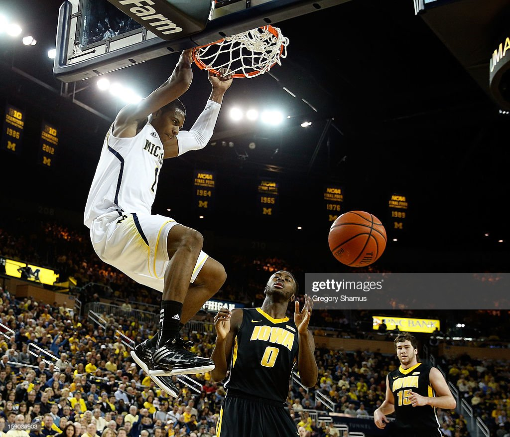Glenn Robinson III #1 of the Michigan Wolverines gets in for a first half dunk next to Gabriel Olaseni #0 of the Iowa Hawkeyes at Crisler Center on January 6, 2013 in Ann Arbor, Michigan.