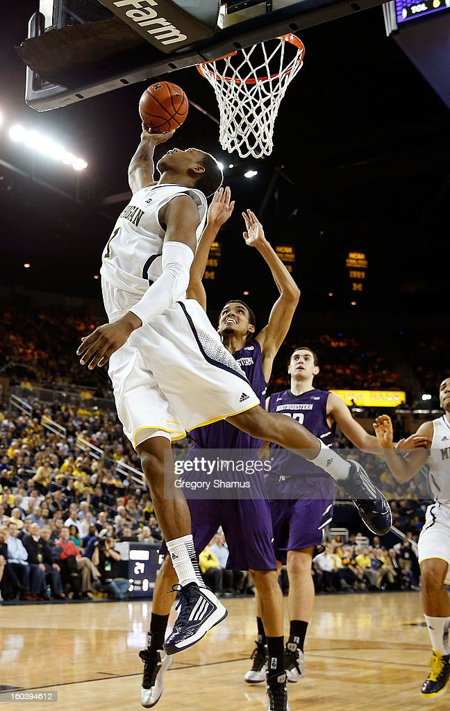 Glenn Robinson III #1 of the Michigan Wolverines gets in for a first half layup in front of Jared Swopshire #12 of the Northwestern Wildcats at Crisler Center on January 30, 2013 in Ann Arbor, Michigan.