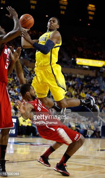 Glenn Robinson III of the Michigan Wolverines tries to get a first half shot off over Richard Howell of the North Carolina State Wolfpack at Crisler...