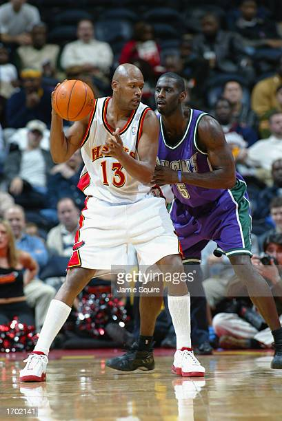 Glenn Robinson of the Atlanta Hawks is defended by Tim Thomas of the Milwaukee Bucks during the NBA game at Phillips Arena on December 5 2002 in...