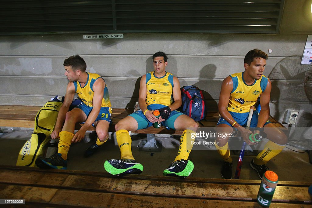 Glenn Simpson (L) and Chris Ciriello (C) of Australia look on in the players dug out after the match between Australia and Pakistan during day three of the Champions Trophy at the State Netball Hockey Centre on December 4, 2012 in Melbourne, Australia.