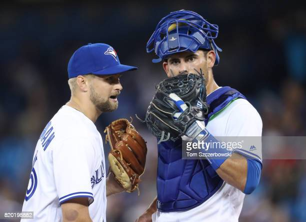 Glenn Sparkman of the Toronto Blue Jays talks to Luke Maile as he comes in to pitch in the eleventh inning during MLB game action against the Boston...