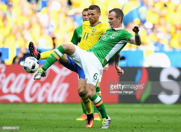 Glenn Whelan of Republic of Ireland and Marcus Berg of Sweden compete for the ball during the UEFA EURO 2016 Group E match between Republic of...