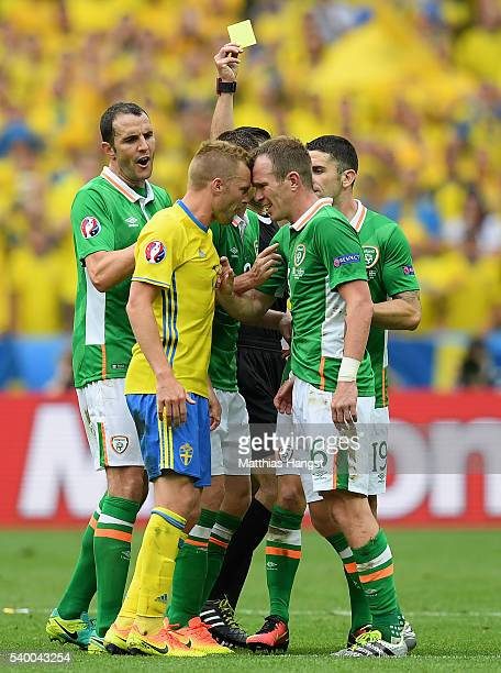Glenn Whelan of Republic of Ireland and Sebastian Larsson of Sweden face off as Whelan is shown a yellow card during the UEFA EURO 2016 Group E match...