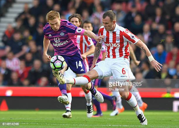 Glenn Whelan of Stoke City attempts to control the ball while pressure from Duncan Watmore of Sunderland during the Premier League match between...