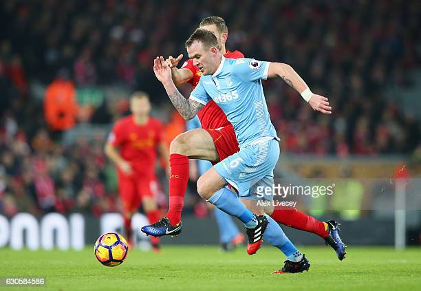 Glenn Whelan of Stoke City is chased by Jordan Henderson of Liverpool during the Premier League match between Liverpool and Stoke City at Anfield on...