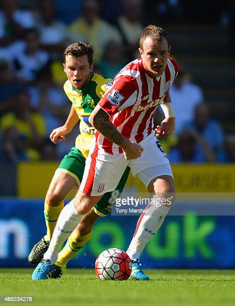 Glenn Whelan of Stoke City tackled by Jonny Howson of Norwich City during the Barclays Premier League match between Norwich City and Stoke City at...