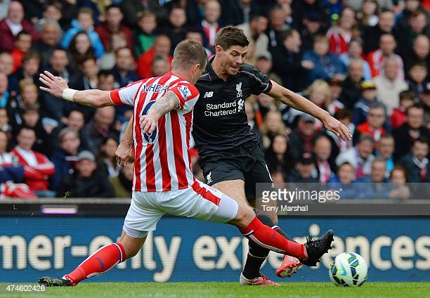 Glenn Whelan of Stoke City tackles Steven Gerrard of Liverpool during the Barclays Premier League match between Stoke City and Liverpool at Britannia...