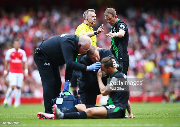 Glenn Whelan of Stoke City talks to referee Jonathan Moss as Marko Arnautovic of Stoke City is given treatment during the Barclays Premier League...