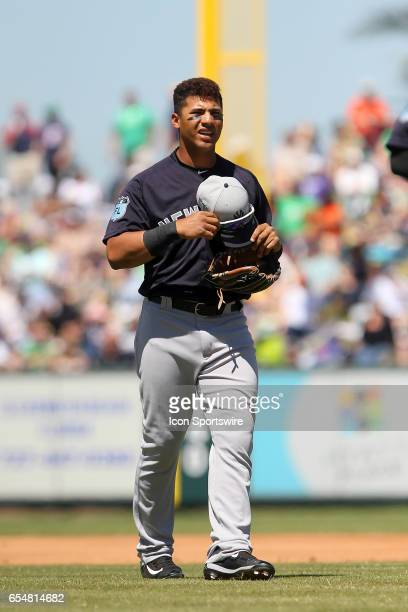 Gleyber Torres of the Yankees gathers his hat and glove after being left on base during the spring training game between the New York Yankees and the...