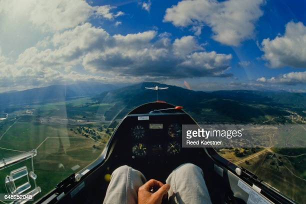 A glider pilot enjoys the view from a sailplane cockpit as he's towed up in the air near a mountain.