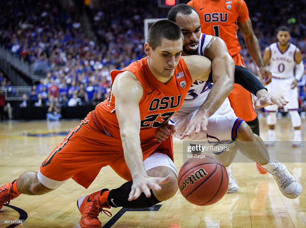 Gligorije Rakocevic of the Oregon State Beavers and Perry Ellis of the Kansas Jayhawks battle for a loose ball in the first half at Sprint Center on...