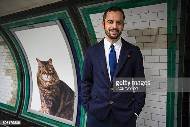 Glimpse founder James Turner poses for a photograph alongside posters of cats on the walls of Clapham Common Underground station in south west London...
