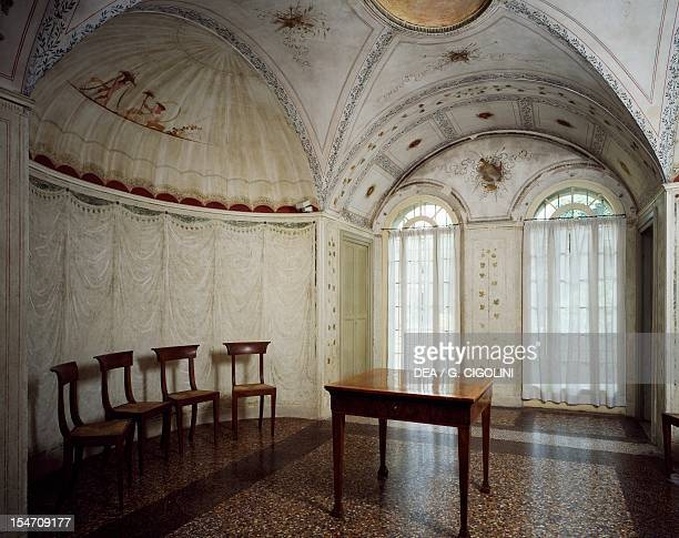 Glimpse of a neoclassical style dining room with chairs table and bench and decorative frescoes by Felice Giani ground floor Palazzo Milzetti Faenza...