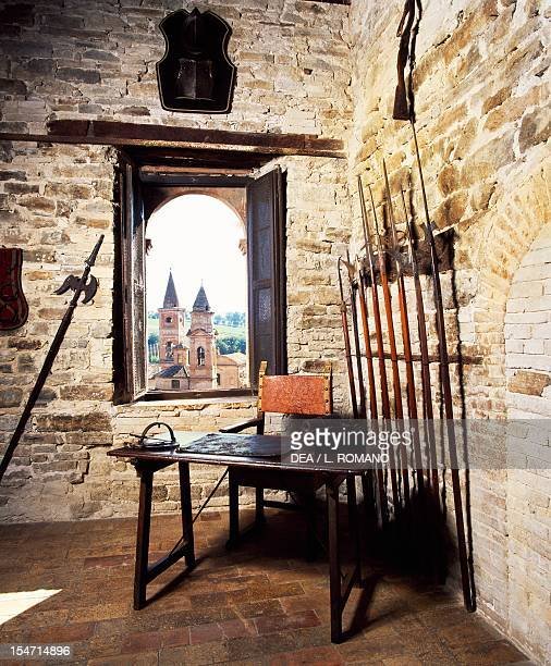 Glimpse of the armory with medieval weapons and the steeples of Caldarola visible through the window Pallotta Castle Caldarola Macerata Marche Italy