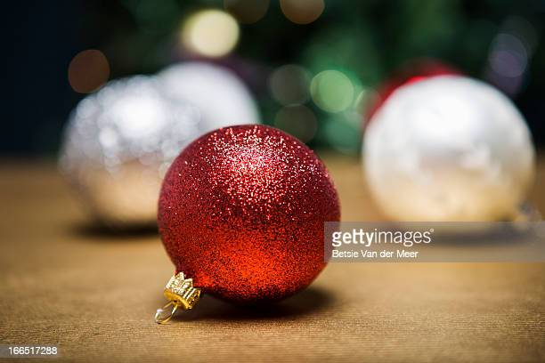 Glitter baubles in front of Christmas tree.