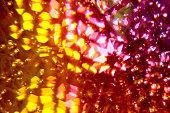Foto tirada através de um vitral de pontos de luz, pisca pisca.