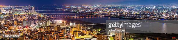 Glittering cityscape bridges illuminated at night Yodo River Osaka Japan