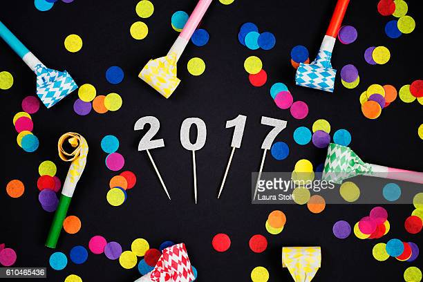 Glittery 2017 numbers amongst colorful confetti and party horns