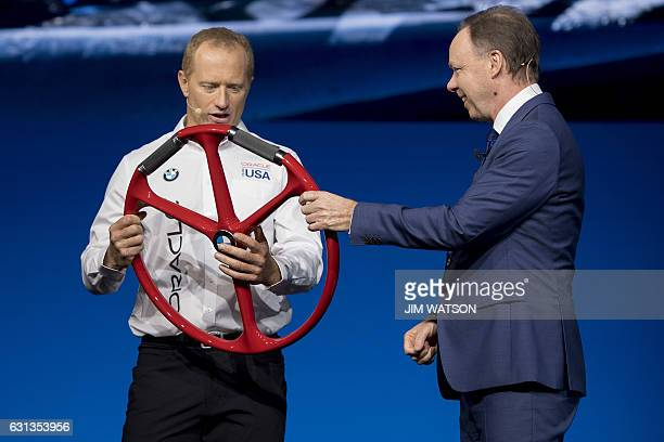 BMW Global Head of Sales and Marketing Dr Ian Robertson gives America's Cup sailor Jimmy Spithill from the Oracle Team USA a steering wheel for the...
